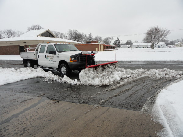 A snow plow clearing a commercial parking lot