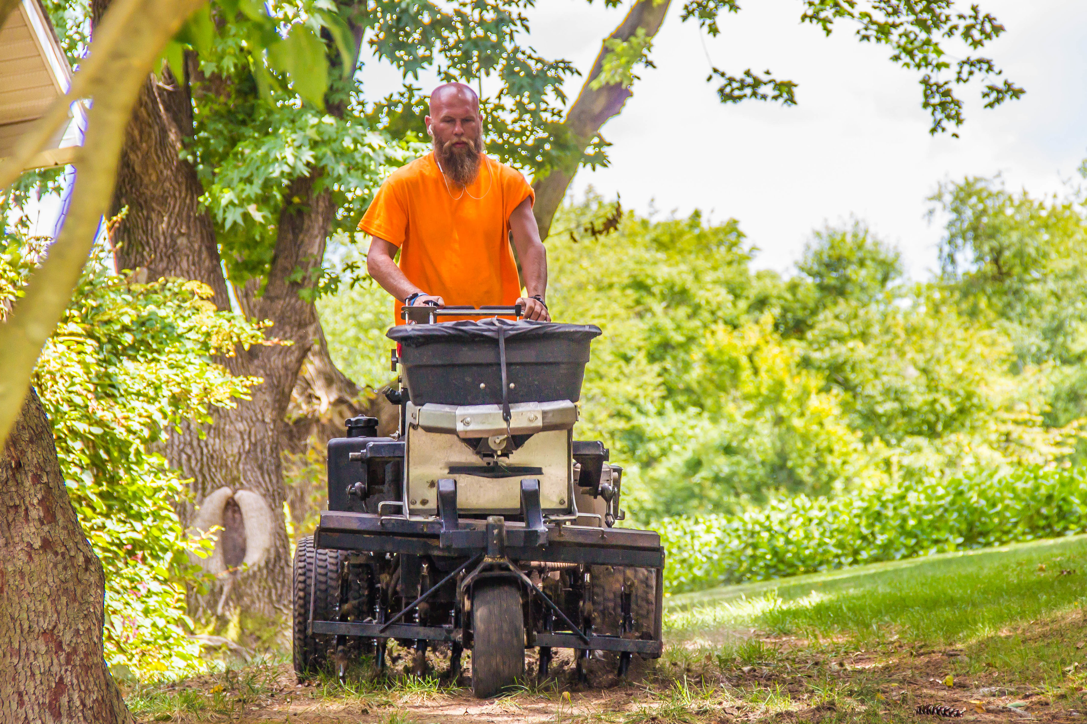 image of a technician aerating a lawn